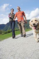Couple walking with golden retriever on road