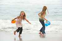 Two girls (7-9 10-12) holding buckets playing on beach