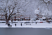Children playing snowball fights around Barnes village pond in snowy winter, London.