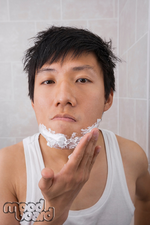 Portrait of mid adult man applying shaving foam on face in bathroom