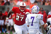 Wolfpack DT Justin Jones (27) eyes Furman's quarterback for a sack.
