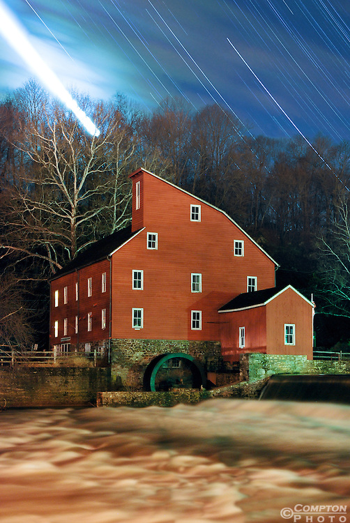 Illustration of the paths of stars and planets moving in the sky behind the Clinton Red Mill. The bright line on the left side of the image is the path of the moon across the sky over 90 min.