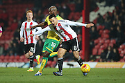 Brentford defender Nico Yennaris (8) battles with Norwich City midfielder Youssuf Mulumbu (18) during the EFL Sky Bet Championship match between Brentford and Norwich City at Griffin Park, London, England on 31 December 2016. Photo by Matthew Redman.