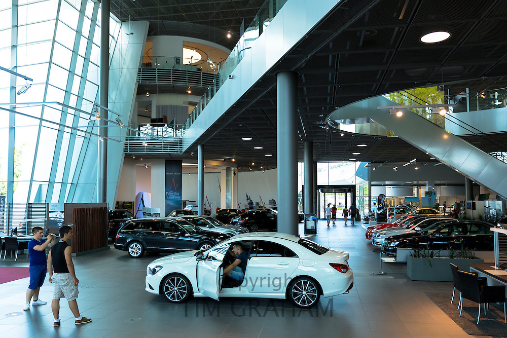 Prospective buyer inspecting a Mercedes CLA 180 Saloon in Mercedes-Benz showroom in Stuttgart, Bavaria, Germany