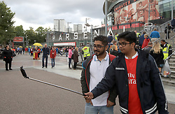 Fans take a selfie outside the stadium prior to the Premier League match at the Emirates Stadium, London.