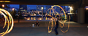 Fire twirler Debbie Kruger (right) practices her fine skills under Marquam Bridge with friend Shireen Press (seated) learning the ropes.