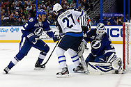 Winnipeg Jets' Eric Tangradi (C) is defended by Tampa Bay Lightning's Eric Brewer (L) as goalie Anders Lindback makes a save during the first period of their NHL hockey game in Tampa, Florida, March 7, 2013.  REUTERS/Mike Carlson (UNITED STATES)