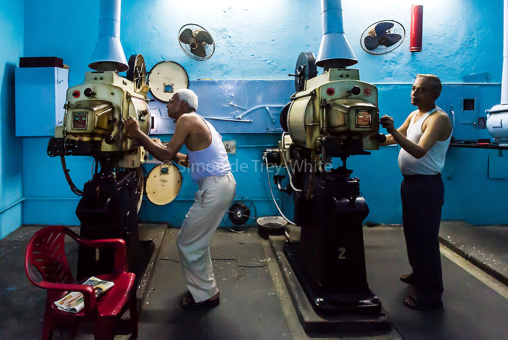 6th September, 2012, Old Delhi, India. Projectionists Shiv Kumar Jaiswal (65, left) and Satish Kumar Sharma (58, right) in the Projection room at the Moti Movie Hall in Old Delhi, India<br /> <br /> Jaiswal has been a projectionist for 38 years, 18 of these at the Moti Movie Hall, Kumar has been a projectionist for 24 years, all at the Moti Movie Hall<br /> <br /> This 'temporary cinema' (one of 5 still remaining in Delhi) and thrives by continuing to provide affordable entertainment (the cheapest ticket costing a mere Rs 20 and a prized balcony seat available at Rs 50.) to people belonging to economically weaker sections in the face of the onslaught of much more expensive multiplexes where seats usually cost Rs 250 rising to over a thousand. The cinema shows mainly Bhojpuri films. <br /> <br /> PHOTOGRAPH BY AND COPYRIGHT OF SIMON DE TREY-WHITE<br /> <br /> + 91 98103 99809<br /> + 91 11 435 06980<br /> +44 07966 405896<br /> +44 1963 220 745<br /> email: simon@simondetreywhite.com photographer in delhi