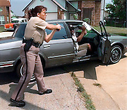 Tulsa County Sheriff's Office deputy Kathleen Ballard holds the passenger of a car at gunpoint after the driver fled following a car chase in Tulsa, OK.