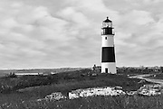 "Sankaty Head Lighthouse on Nantucket island, Cape Cod, Massachusetts, USA in black and white with old brick walls and a view of the moors in the fall. The 70 foot tall brick lighthouse was built in 1850. It was the first lighthouse in Massachusetts with a Fresnel lens, which was replaced in 1950 with a rotating aerobeacon. The light was automated in 1965 but Coast Guard personnel occupied the station until 1992. In 2007, the Sankaty Head light house was moved from the edge of an eroding bluff to its current location, 250 feet from the bluff's edge. Sankaty, from the Native American Nantucket Indian word ""sankoty,"" means ""highland."""