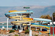 Israel, Slides in a water park at the sea of Galilee Golan Heights in the background