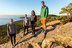 "A group of hikers pose on a ledge on ""The Beehive"" in fall in Maine's Acadia National Park."