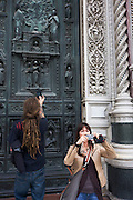 Tourists gaze upwards to the Baptistry of San Giovanni beneath Florence's Santa Maria del Fiore (Duomo) Cathedral. ..The Basilica di Santa Maria del Fiore is the cathedral church (Duomo) of Florence, Italy, begun in 1296 in the Gothic style to the design of Arnolfo di Cambio and completed structurally in 1436 with the dome engineered by Filippo Brunelleschi.
