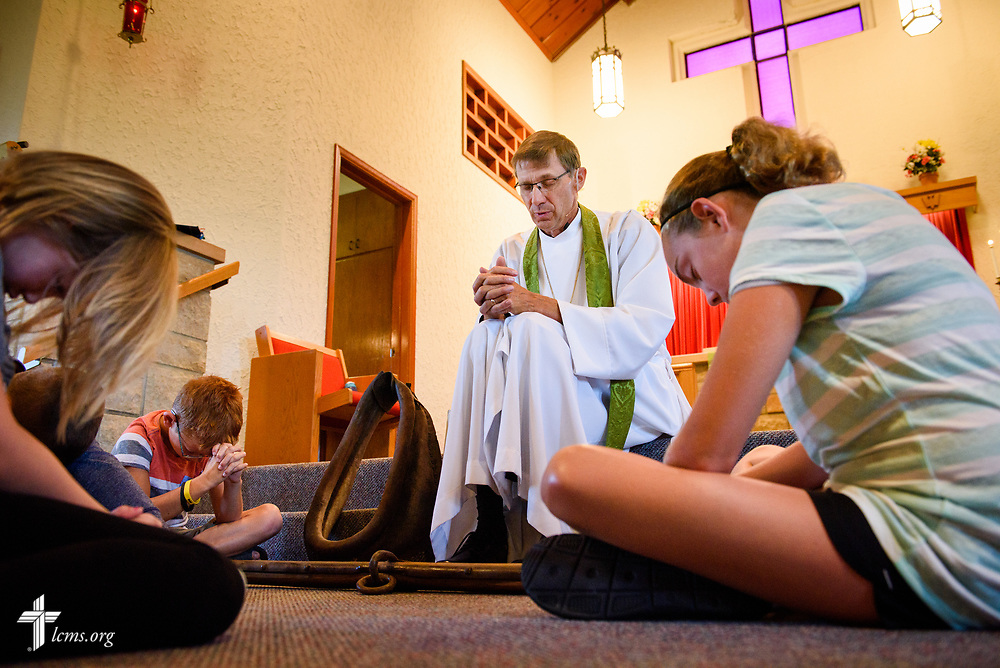 The Rev. Steven Struecker, full-time farmer and pastor of <br /> Immanuel Lutheran Church, Livermore, Iowa, and Zion Evangelical Lutheran Church, Lu Verne, Iowa, prays during a children's message on Sunday, July 9, 2017. LCMS Communications/Erik M. Lunsford