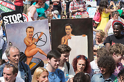 © Licensed to London News Pictures. 21/06/2014. London, England. Painter Kaya Mar carries two of his political paintings through the crowd in Parliament Square.  The No More Austerity demonstration & march takes place in Central London. It was organised by the People's Assembly and it is estimated that approx. 50,000 people joined the protest. Photo credit: Bettina Strenske/LNP