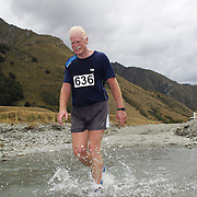 Runner Rob Donald crosses Moke Creek on the Ben Lomond High Country Station during the Pure South Shotover Moonlight Mountain Marathon and trail runs. Moke Lake, Queenstown, New Zealand. 4th February 2012. Photo Tim Clayton