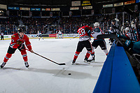 KELOWNA, CANADA - MARCH 2: Lane Gilliss #9 scoops the puck as Clay Hanus #58 of the Portland Winterhawks checks Cole Carrier #12 of the Kelowna Rockets into the boards during first period  on March 2, 2019 at Prospera Place in Kelowna, British Columbia, Canada.  (Photo by Marissa Baecker/Shoot the Breeze)
