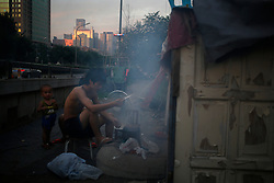 A picture made available on 30 July 2013 of a Chinese resident cooking in a slum or shanty town area by the second ring road of Beijing, a few hundred metres away from the prosperous Central Business District (CBD), separated only by a busy highway in China, 29 July 2013. Beijing announced plans to spend 500 billion yuan (61.5 billion euros) to renovate shanty towns within the fourth ring road according to local media. The five-year plan is expected to affect more than 230,000 households. China's massive urbanization push has resulted in the creation of large pockets of shanty towns and slums in urban areas as millions of migrant workers shifting to the cities are often priced out of city-centre properties. Slum or shanty town dwellers often live in dirty and cramped conditions, where they have no running water in their homes and have to share toilet and shower facilities.