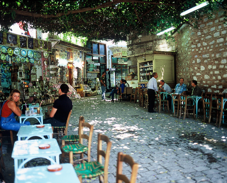 Couple and a small group of men eating a street cafe in Agiassos on the island of Lesvos in Greece.