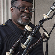 Scottish-African American bagpiper at the Tartan Day Parade. Tartans are precisely woven sets of color each one signifying an association with a Clan, Society... no two Tartan are alike.<br />