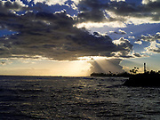 Sunset through the clouds at Kekaha Harbor, on the southwest side of Kauai, Hawaii, USA.