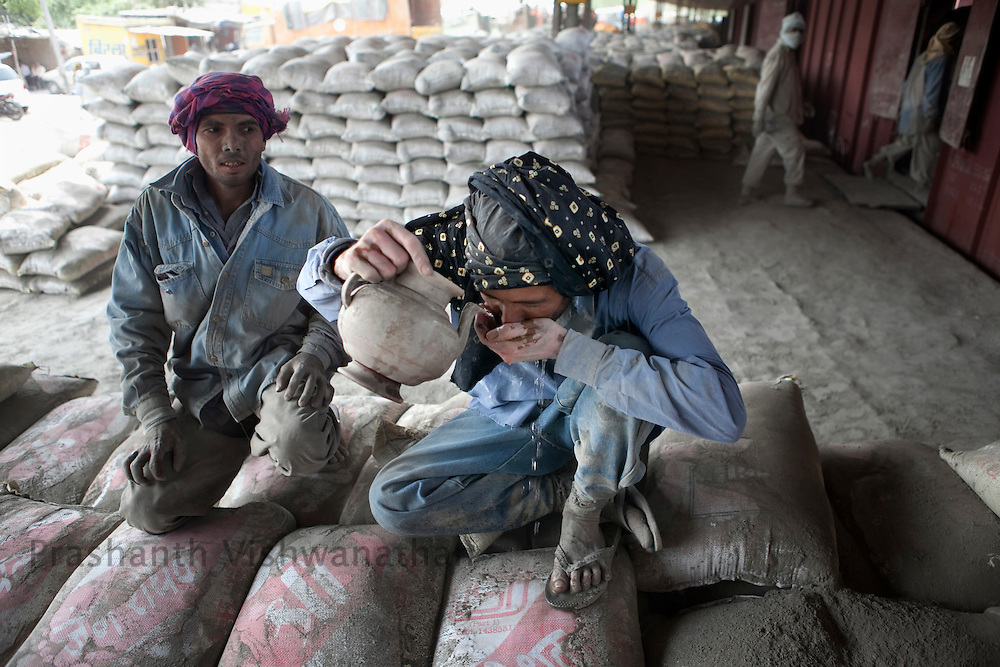 Labourers drink water sitting on cement bags after unloading then manually from freight trains at the Shakur Basti station in New Delhi, India, on Tuesday April 5, 2011.  Photographer: Prashanth Vishwanathan/Bloomberg News