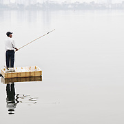 A fisherman stands on a small floating platform to cast his line from a bamboo fishing rod on West Lake (Ho Tay) in Hanoi, Vietnam. The thick haze obscures the far shore. Heavy pollution in the lake makes the fish caught there of questionable quality.