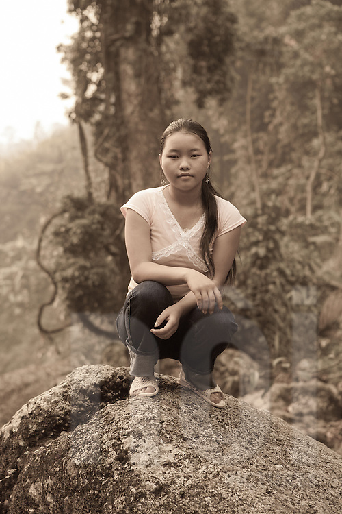 Portrait of a Hmong teenager squatting on top of a rock smirking at the camera, Than Uyen area, Lai Chau, Vietnam, Southeast Asia