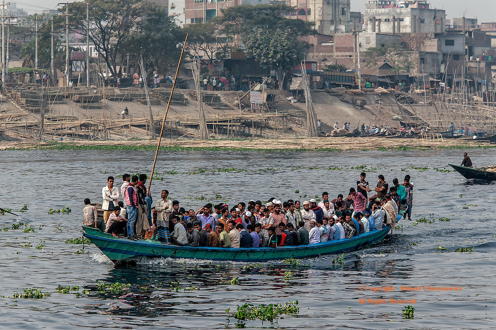 Men Only: Amongst the smaller boats that ply the Buriganga River, a large wooden boat is fully loaded with only men, Dhaka Bangladesh.