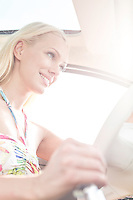 Low angle view of happy woman driving car