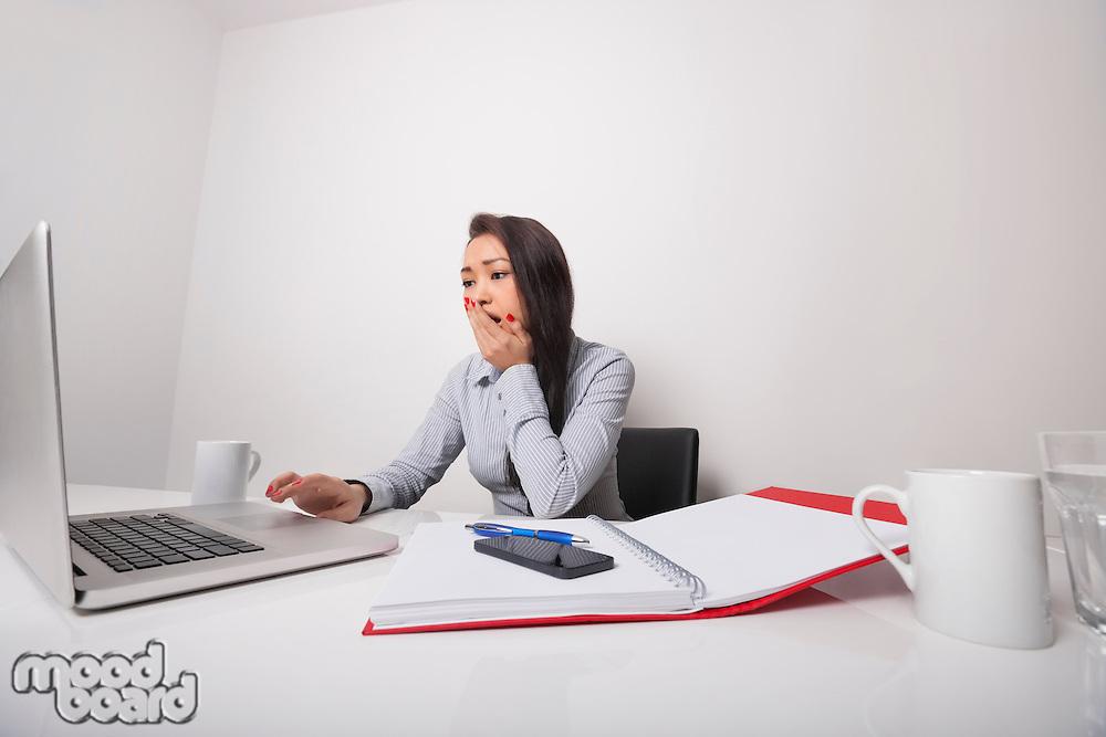 Sleepy businesswoman working on laptop at office desk