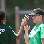 Opposing players high five at first base during the Norwalk Little League baseball 'Champions' team V Greenwich in the Challenger Division  Recognition Day competition. The day acknowledged the many talents of the great players on the Challenger Division teams. The division has weekly games and practices for kids with special needs. Challenger division are held throughout the country.  Broad River Fields, Norwalk, Connecticut. USA. 2nd June 2013. Photo Tim Clayton