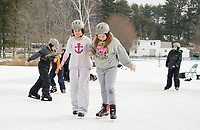 Olivia gives a helping hand to Riley as she ice skates for the first time at Bolduc Park on Thursday morning.  Elm Street School fifth graders experienced the winter Olympics sports of ice skating, snowshoeing and cross country skiing.    (Karen Bobotas/for the Laconia Daily Sun)