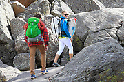 Two rock climbers head up the trail to the base of Devils Tower before attempting to climb the monument.