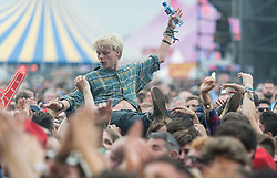 © Licensed to London News Pictures. 30/08/2015. Reading, UK. A festival goer crowd surfs as  The Maccabees performing at Reading Festival 2015, Day 3 Sunday, shrouded in stage effects smoke.  In this picture - Hugo White.  Photo credit: Richard Isaac/LNP
