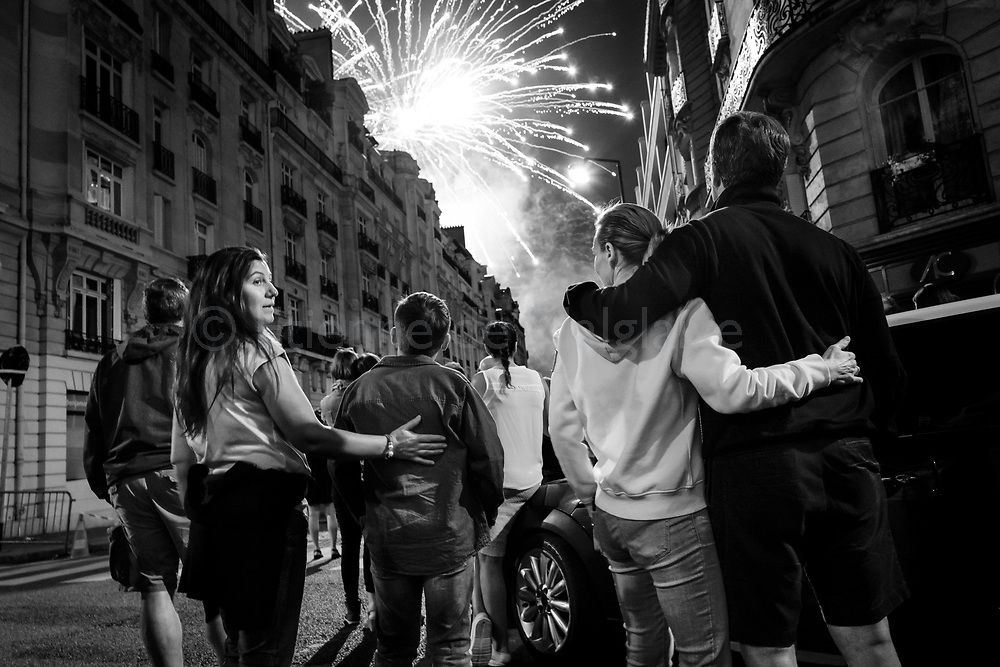 From a nearby street, onlookers watch a spectacular fireworks shot from the Eiffel Tower on Bastille Day in Paris, 14 July 2017.