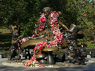 Alice in Wonderland sculpture in Central Park, decorated with a garland of flowers.