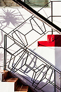 A palm tree and a Miami Modern stair railing cast shadows on a small apartment building in Miami Beach