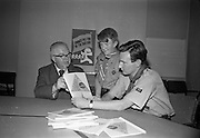 13/07/1967<br /> 07/13/1967<br /> 13 July 1967<br /> Presentation of booklet by Mr H.E.F. Hall, Chairman, National Savings Committee to Dr Conal Hooper, Director of Organisation, Catholic Boy Scouts of Ireland. 5000 copies of the booklet were presented at the National Savings Committee Headquarters in Dublin, to commemorate the C.B.S.I. 40th Anniversary National Camp at Lismore castle, Co. Waterford and as a gesture of appreciation of the work of Scouting Organisations in promoting thrift. The booklet consisted of a series of folders dealing with different trees in Ireland (first series covered 6 trees). <br /> Picture shows Mr Hall (left) discussing the booklet with Dr Hooper with A.P.L. Sean Flanagan, 7th Dublin (St. Mary's) Troop in centre.
