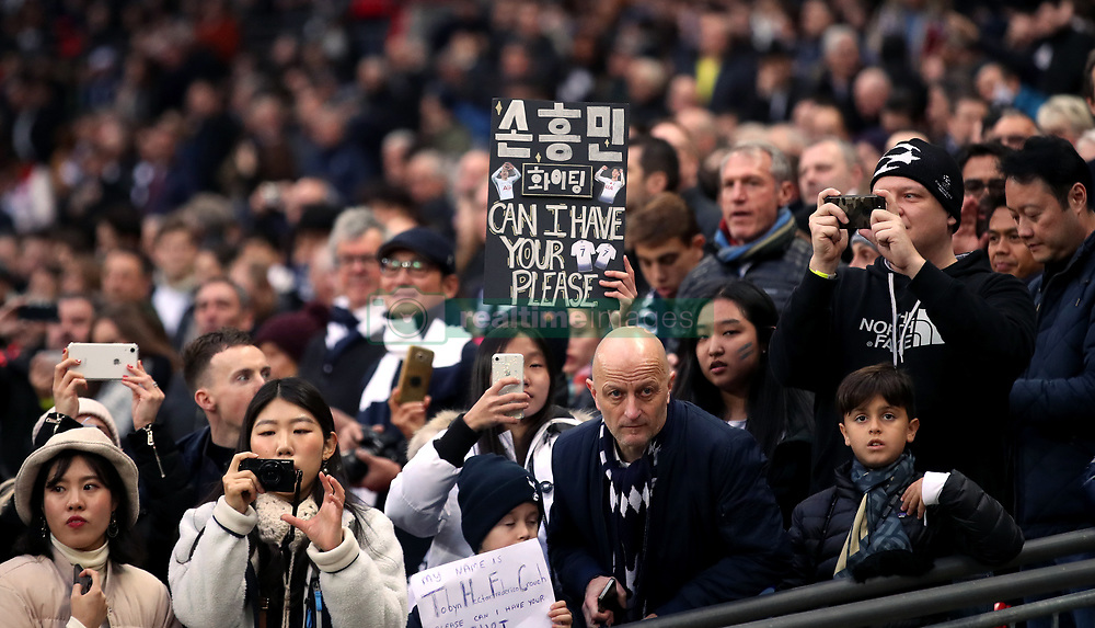 A Tottenham Hotspur fan holds up a sign asking for the shirt of Son Heung-min
