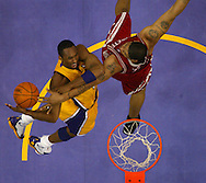 The Lakers' Kobe Bryant is fouled en-route to the basket.
