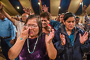 "12 JULY 2012 - FT DEFIANCE, AZ:  People pray during the alter call at the 23rd annual Navajo Nation Camp Meeting in Ft. Defiance, north of Window Rock, AZ, on the Navajo reservation. Preachers from across the Navajo Nation, and the western US, come to Navajo Nation Camp Meeting to preach an evangelical form of Christianity. Evangelical Christians make up a growing part of the reservation - there are now more than a hundred camp meetings and tent revivals on the reservation every year. The camp meeting in Ft. Defiance draws nearly 200 people each night of its six day run. Many of the attendees convert to evangelical Christianity from traditional Navajo beliefs, Catholicism or Mormonism. ""Camp meetings"" are a form of Protestant Christian religious services originating in Britain and once common in rural parts of the United States. People would travel a great distance to a particular site to camp out, listen to itinerant preachers, and pray. This suited the rural life, before cars and highways were common, because rural areas often lacked traditional churches.    PHOTO BY JACK KURTZ"