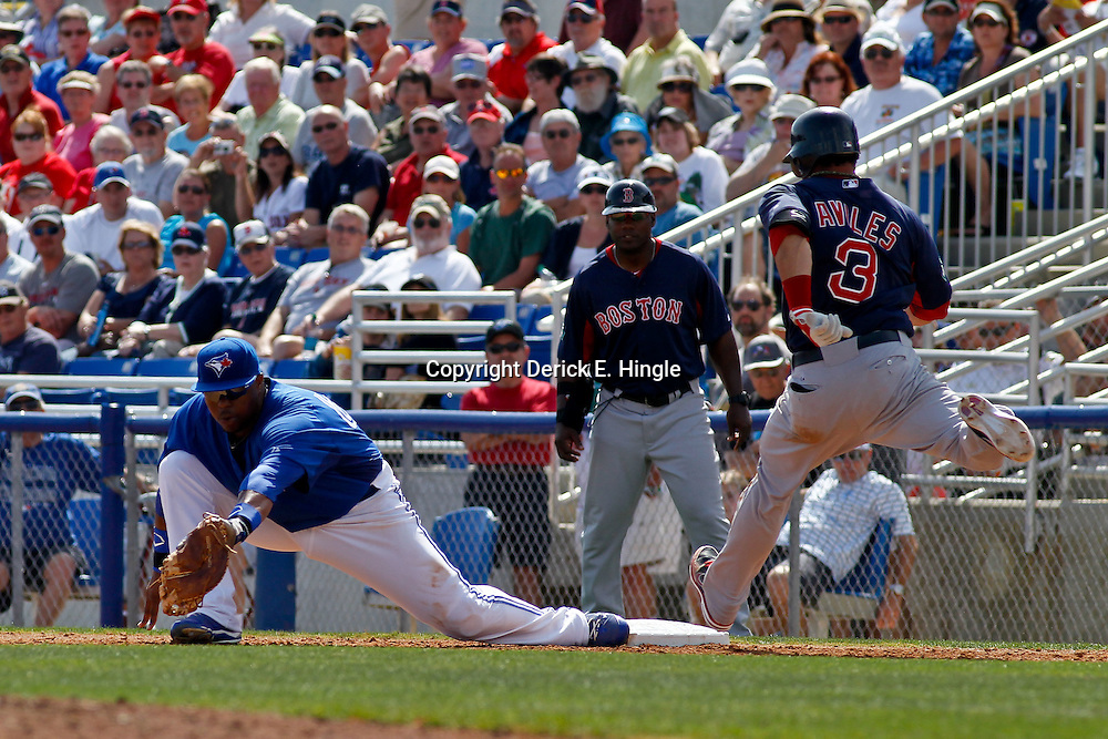 March 7, 2011; Dunedin, FL, USA; Toronto Blue Jays first baseman Edwin Encarnacion (10) gets an out against Boston Red Sox shortstop Mike Aviles (3)during the top of the fourth inning of a spring training game at Florida Auto Exchange Stadium. Mandatory Credit: Derick E. Hingle-US PRESSWIRE