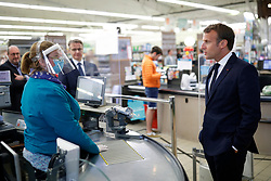 French President Emmanuel Macron talks with a cashier wearing a protective face mask as he visits a Super U supermarket about the partnership with local producers in Saint-Pol-de-Leon during a day trip centered on agriculture amid the coronavirus disease (COVID-19) outbreak in Brittany, France, April 22, 2020. Photo by Stephane Mahe/Pool/ABACAPRESS.COM