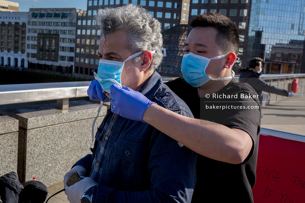 As the UK government lead by Prime Minister Boris Johnson urges Britons to avoid non-essential travel to EU countries, and to avoind contact with others in public places like pubs and theatres during the Coronavirus pandemic, Malaysians wearing their own surgical masks hand out free masks to commuters on London Bridge, on 16th March 2020, in London, England. Within 45mins they had given out 1,000 to passing Londoners.