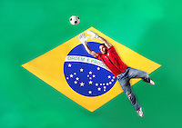 Goalkeeper saving ball in front of Brazilian flag