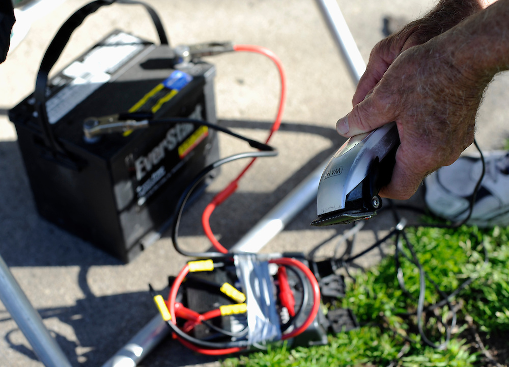 Anthony Cymerys checks his clippers that are connected to a car battery through a power inverter in Hartford, Conn., Wednesday, May 1, 2013.