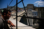 "Tourists looking out at the Neretva river...Divers and tourists at Mostar's famous Old Bridge (Stari Most) in Bosnia and Herzegovina. This bridge is the city and region's biggest tourist attraction and there are busses full of tourists coming in from Sarajevo and Dubrovnik, Croatia. For 25euros tourists can train to jump from the bridge themselves, under supervision from the ""professional"" Mostar divers known as the Mostari. .."