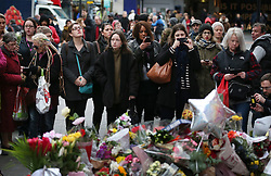 © Licensed to London News Pictures. 12/01/2016. London, UK. People gather in tribute near a mural of David Bowie in Brixton where he was born. Photo credit: Peter Macdiarmid/LNP