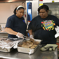 Lauren Wood   Buy at photos.djournal.com<br /> Willethal Johnson, left, and cafeteria manager Nikki Bilger take pans of hamburgers out of the oven to check the temperature Friday morning at Tupelo High School.